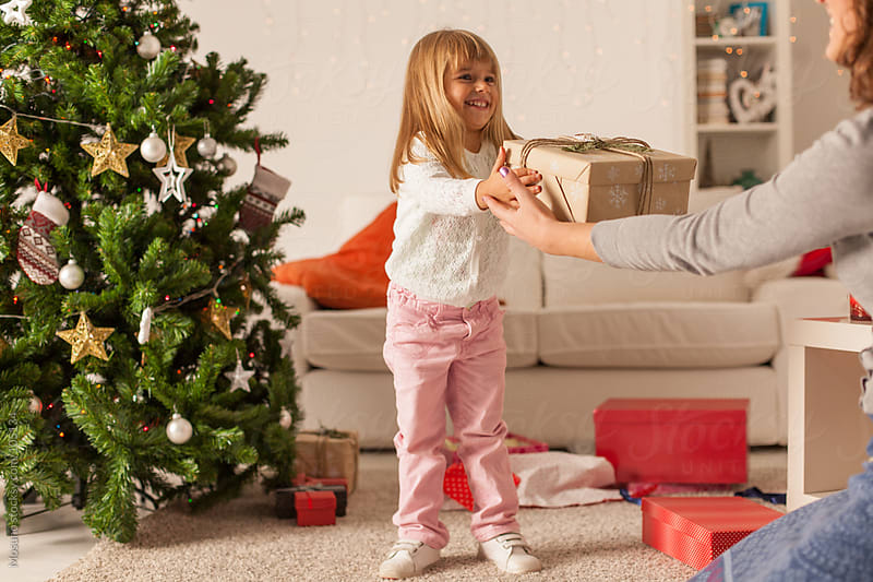 Cute Girl Giving Christmas Present to Her Mother by Mosuno for Stocksy United