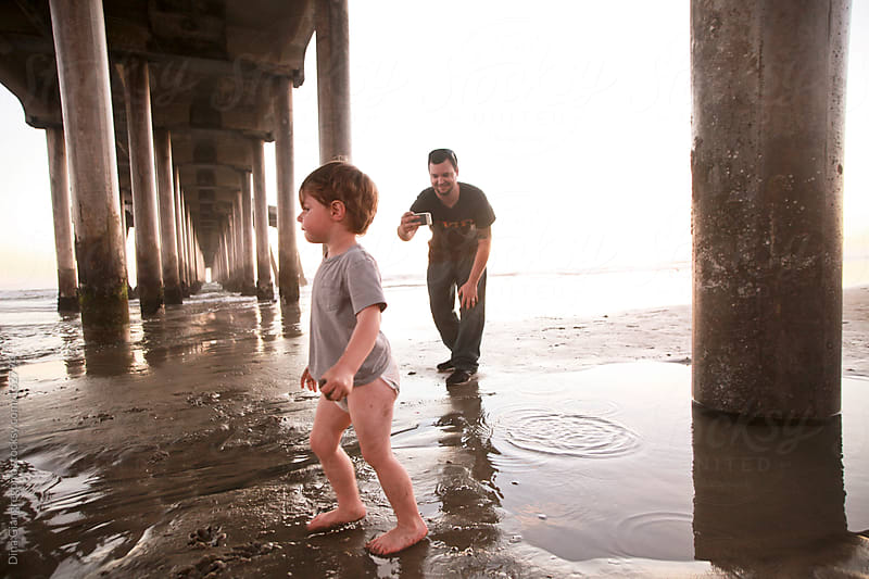 Father taking picture of son at the beach by Dina Giangregorio for Stocksy United