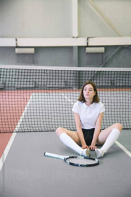 Tennis player sitting on floor against net by Danil Nevsky for Stocksy United
