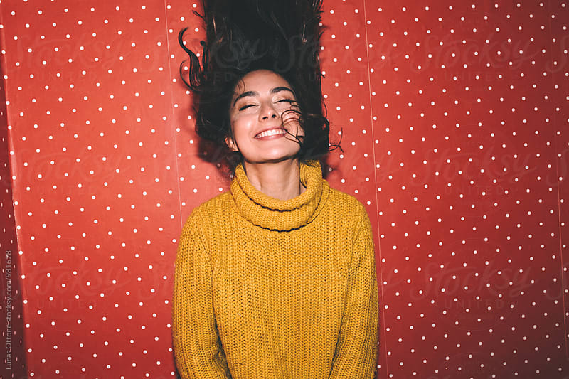Young woman over a red polka dots wallpaper by Lucas Ottone for Stocksy United