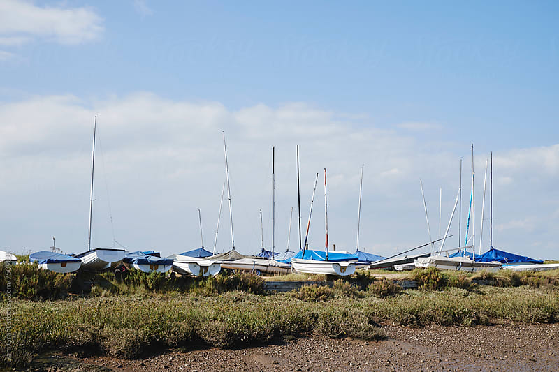 Sailing boats stored on land. Brancaster Staithe, Norfolk, UK. by Liam Grant for Stocksy United