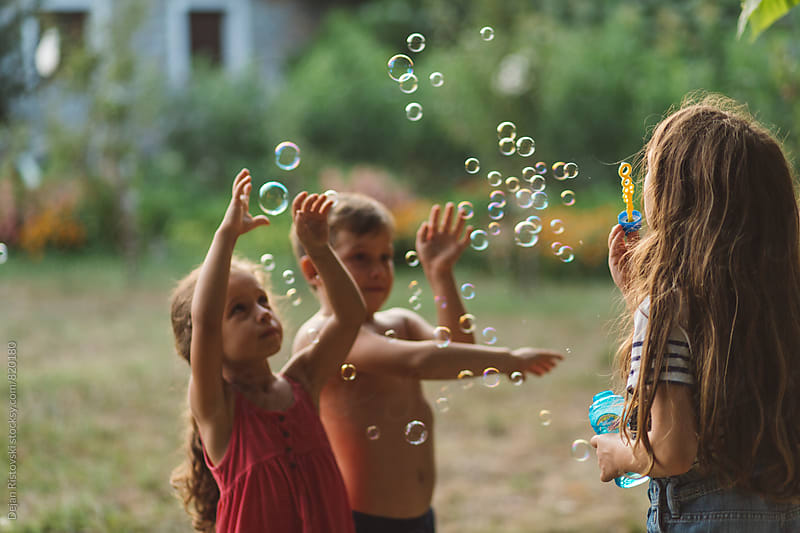 Children playing with bubbles in the yard. by Dejan Ristovski for Stocksy United