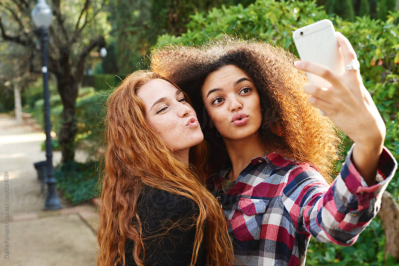 Two funny girlfriends making selfie in park by Guille Faingold for Stocksy United