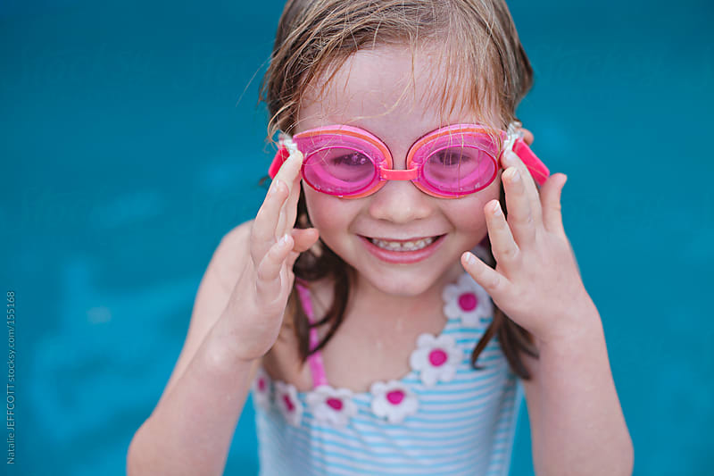 A young girl puts on her pink goggles ready to to go swimming  by Natalie JEFFCOTT for Stocksy United