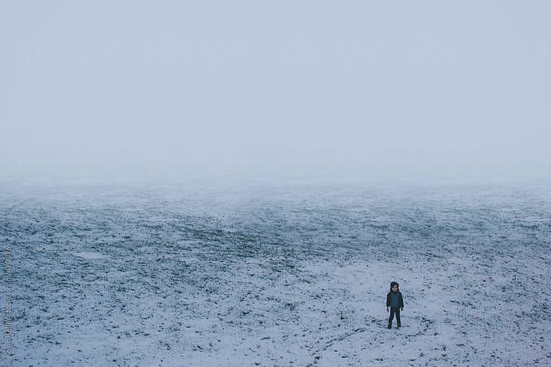Young Boy Standing in a Snow Covered Field by Kevin Keller for Stocksy United