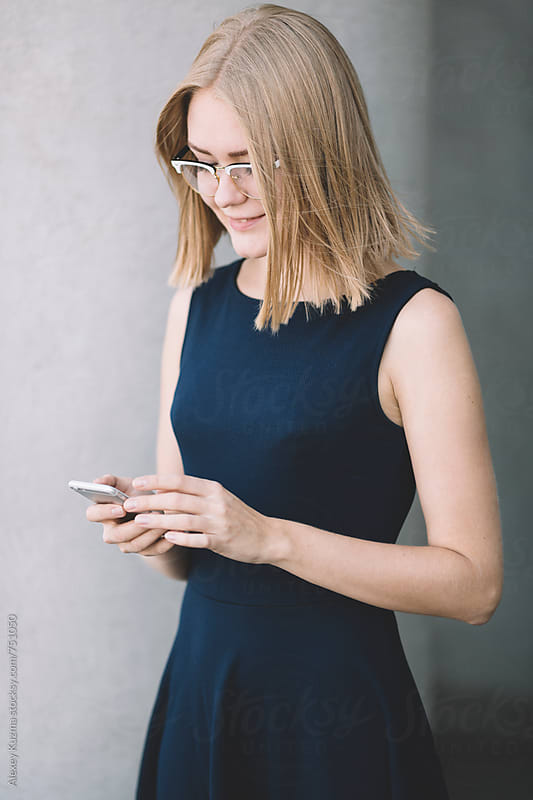 Happy businesswoman sending a message with smartphone on the street. by Alexey Kuzma for Stocksy United