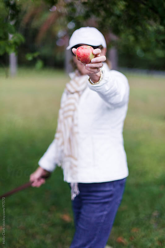 A woman holds an apple out in front of her. by Holly Clark for Stocksy United