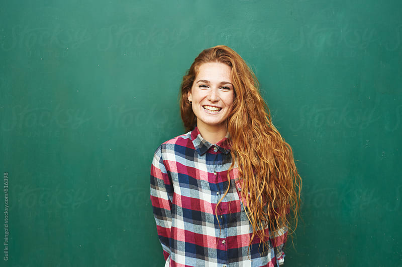 Red-haired smiling woman in checked shirt by Guille Faingold for Stocksy United