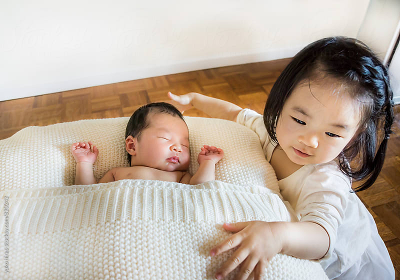 Asian siblings - BIg sister taking care of her newborn baby sister by yuko hirao for Stocksy United