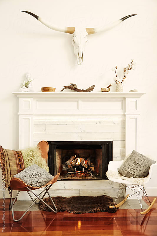 Living room with fireplace, steer head, and chairs by Trinette Reed for Stocksy United
