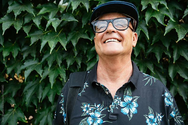 Happy and stylish senior man laughing, wearing a beret and glasess, in front of an ivy background by Inuk Studio for Stocksy United
