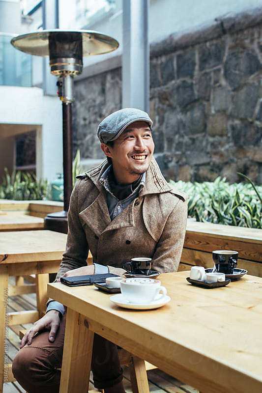 Stylish Young Asian Man Sitting on Restaurant Terrace and Smiling by VISUALSPECTRUM for Stocksy United