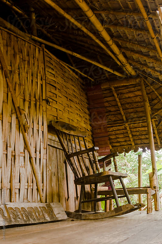 Wooden rocking chair on the porch of a nature house made of bamboo by Søren Egeberg Photography for Stocksy United