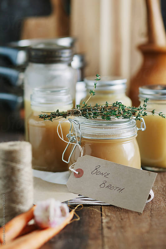 Bone broth: Bone broth in jars on kitchen table, with written food label. by Darren Muir for Stocksy United