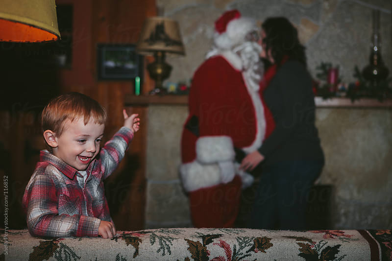 Little Boy Sees Santa Kissing Momma by Shelly Perry for Stocksy United