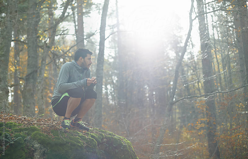 Athlete taking a break in the forest by Miquel Llonch for Stocksy United