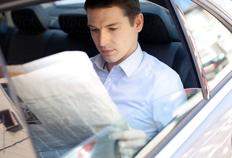 Businessman sitting in a backseat of the car and reading newspapers.  by Mosuno for Stocksy United