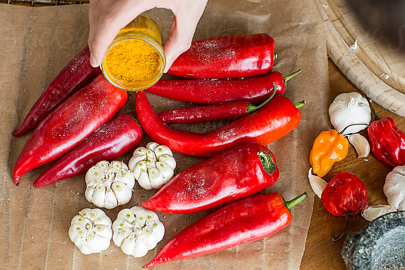 Hand sprinkling turmeric on peppers and garlic by Lior + Lone for Stocksy United