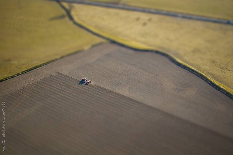 Aerial view of a tractor plowing a farmer's field by Andy Campbell for Stocksy United