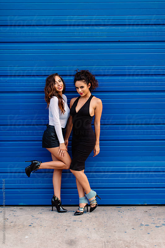 Two beautiful women in dressed up attire & heels.  by Kristen Curette Hines for Stocksy United