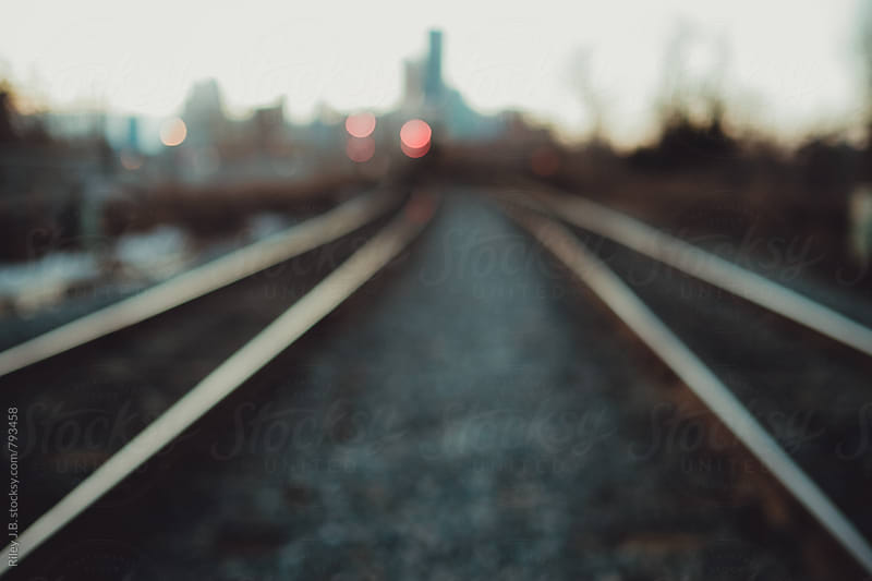 Dual train tracks in a city, out of focus by Riley Joseph for Stocksy United