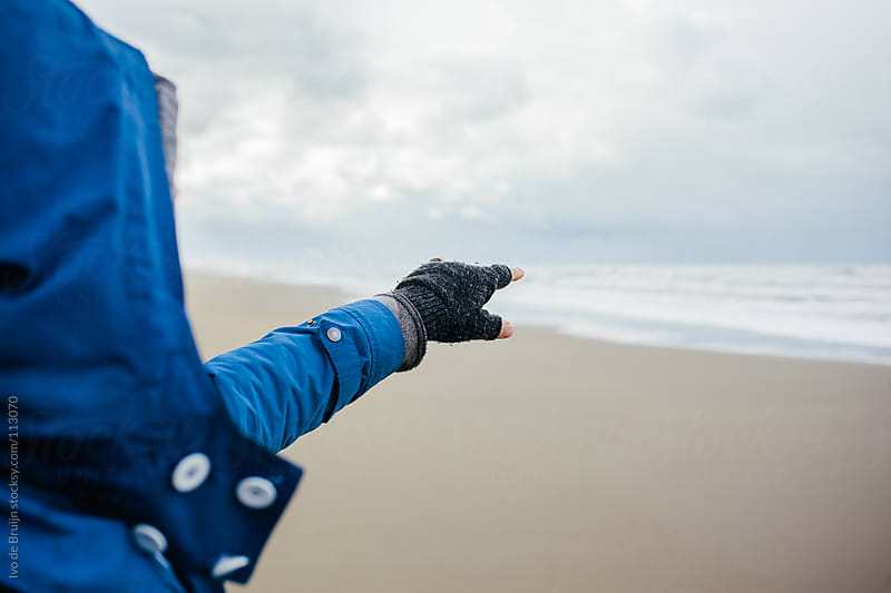 Man pointing at a point in the ocean on a cloudy day by Ivo de Bruijn for Stocksy United