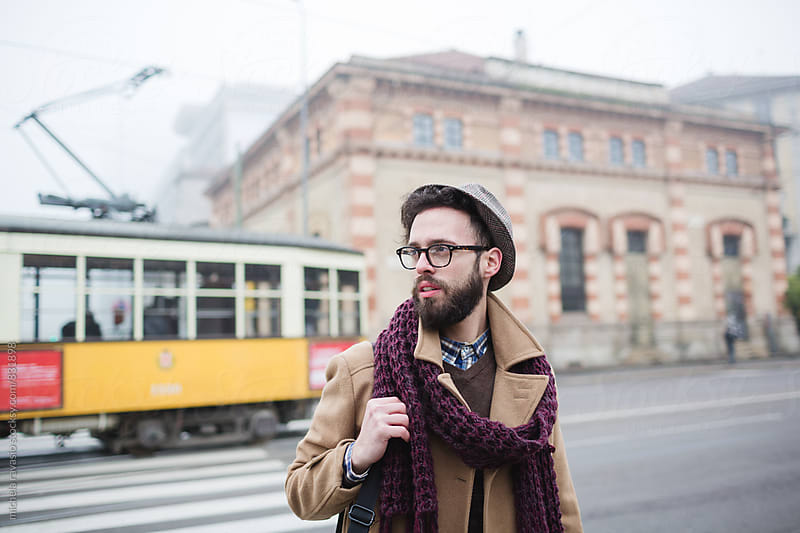 Young man walking down the city on a cold day by michela ravasio for Stocksy United