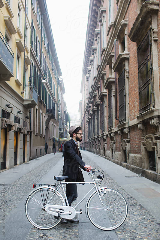 Profile of young man with his bicycle in the street by michela ravasio for Stocksy United
