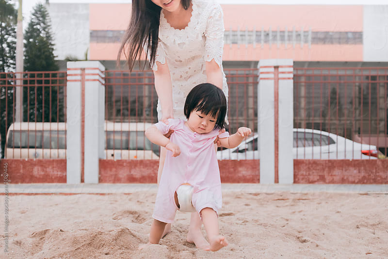 Asian baby girl learning walking by Xunbin Pan for Stocksy United