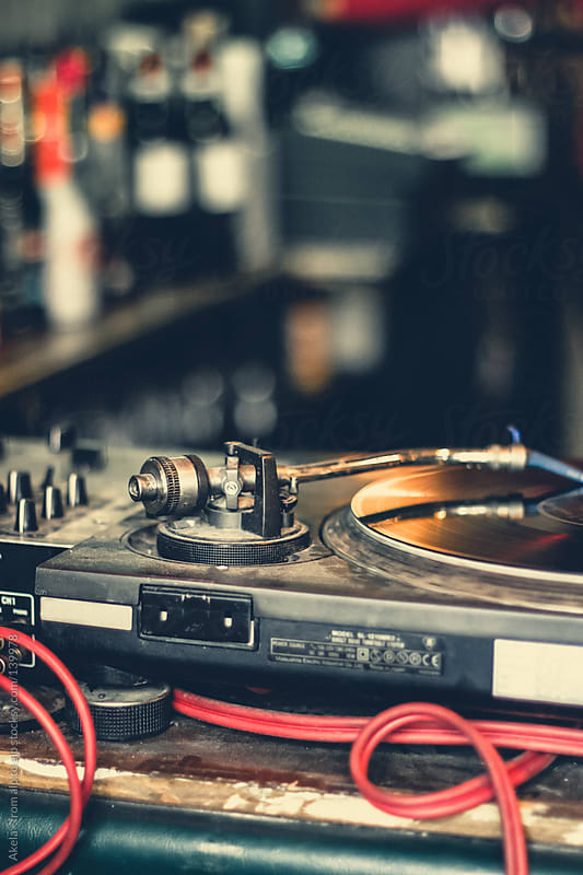 DJ equipment with turntable and mixing console by Leander Nardin for Stocksy United