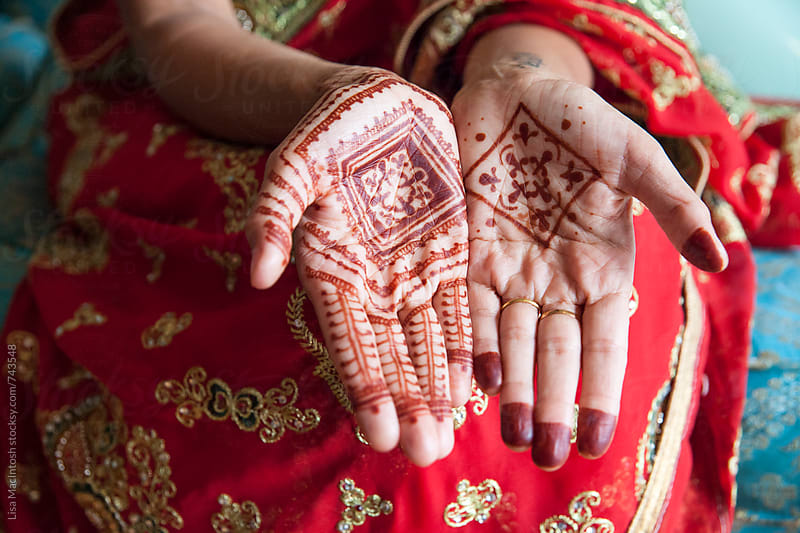 hands with traditional henna designs by Lisa MacIntosh for Stocksy United