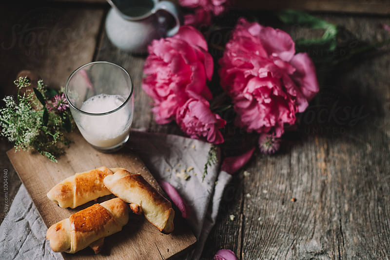 Baked rolls and a glass of milk by Natasa Kukic for Stocksy United