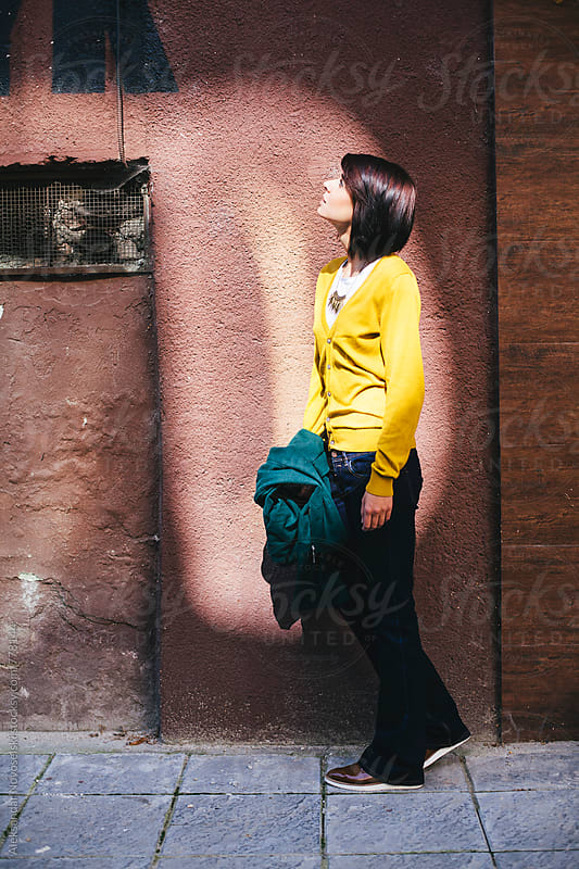 Young woman with yellow jacket and green coat in urban environment by Aleksandar Novoselski for Stocksy United