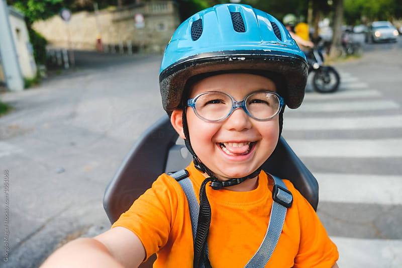 Toddler with Helmet on Rear Seat of a Bicycle, Child Safety by Giorgio Magini for Stocksy United