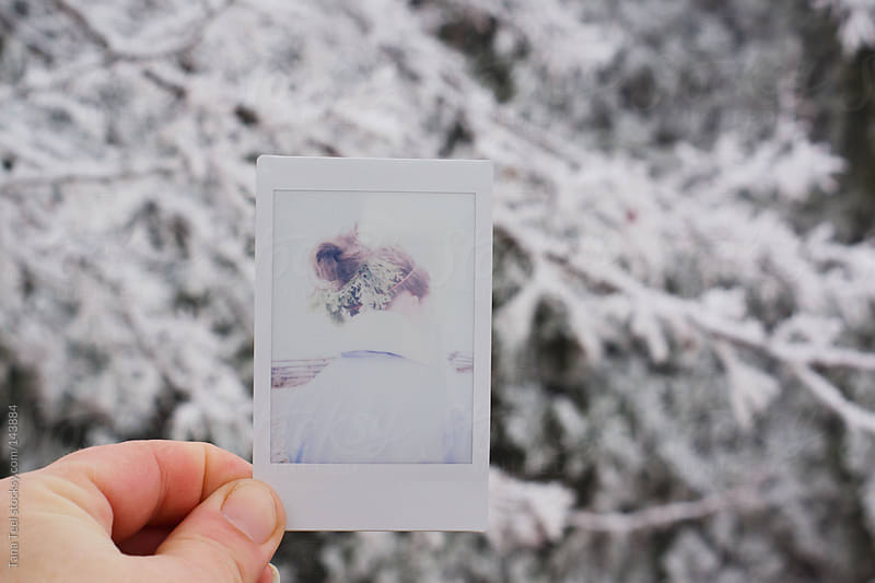 A mini Polaroid of a girl against evergreen trees by Tana Teel for Stocksy United