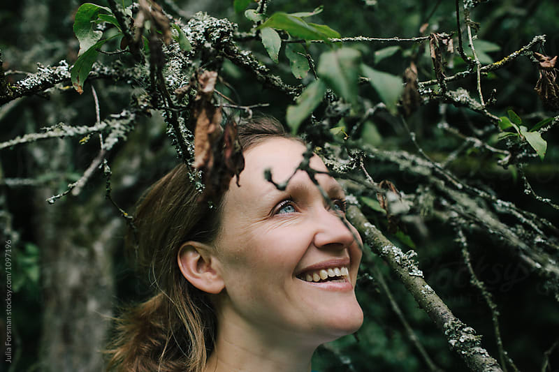 Woman smiling naturally standing under the branches of a tree. by Julia Forsman for Stocksy United
