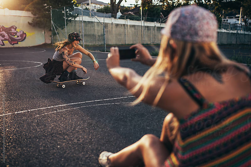 Happy young girl skateboarding with friend taking photos  by Jacob Lund for Stocksy United