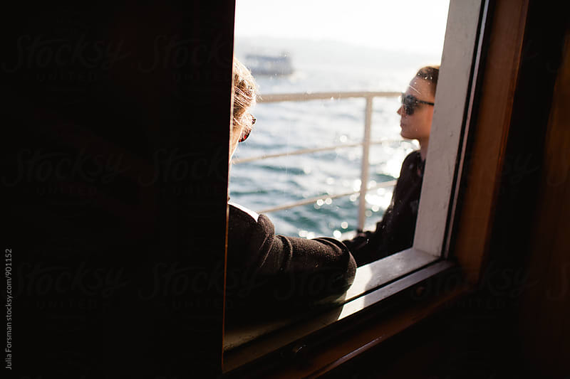Two women, just seen, look out over the Bosphorus on their Istanbul ferry journey. by Julia Forsman for Stocksy United