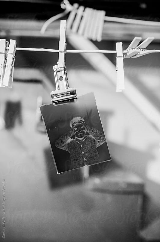 4x5 sheet film negative hanging to dry in the basement by Cameron Whitman for Stocksy United