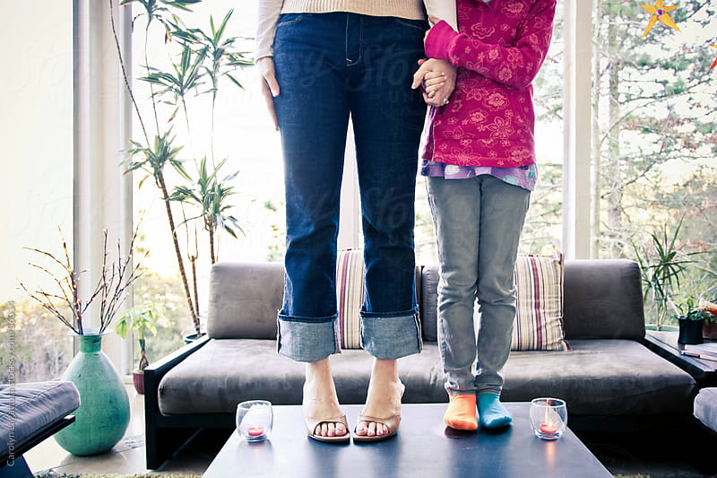Mother and her daughter, standing on a table and holding hands. by Carolyn Lagattuta for Stocksy United
