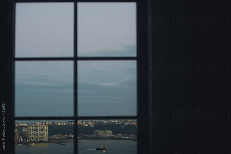 View of boat, lake, buildings out the window by Lauren Naefe for Stocksy United