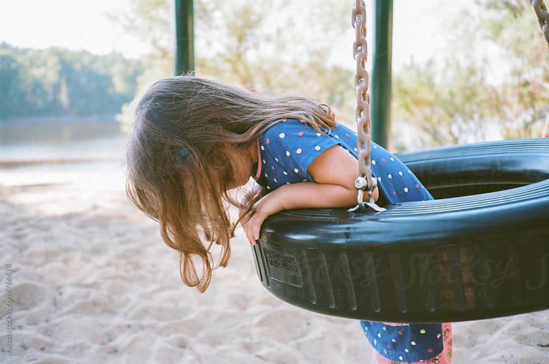 Young girl hanging off a tractor tire swing in a park by Jakob for Stocksy United