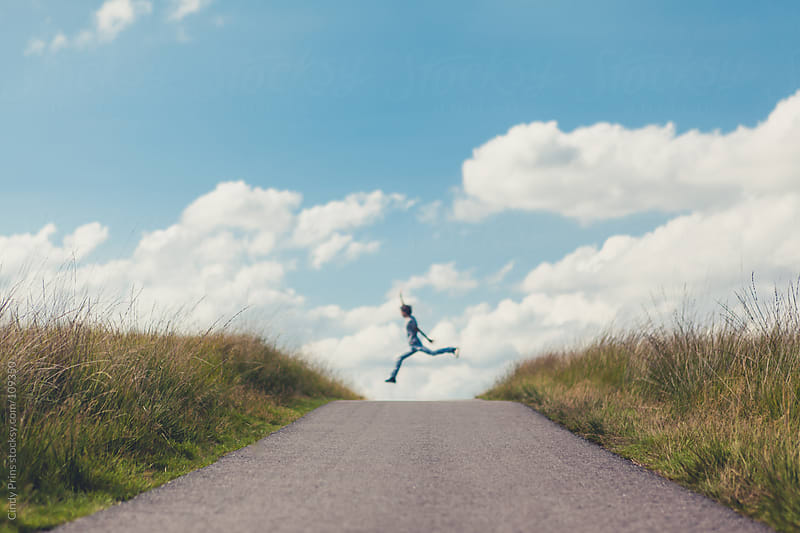 Teenage boy jumping over a road in the dunes against a blue summer sky by Cindy Prins for Stocksy United