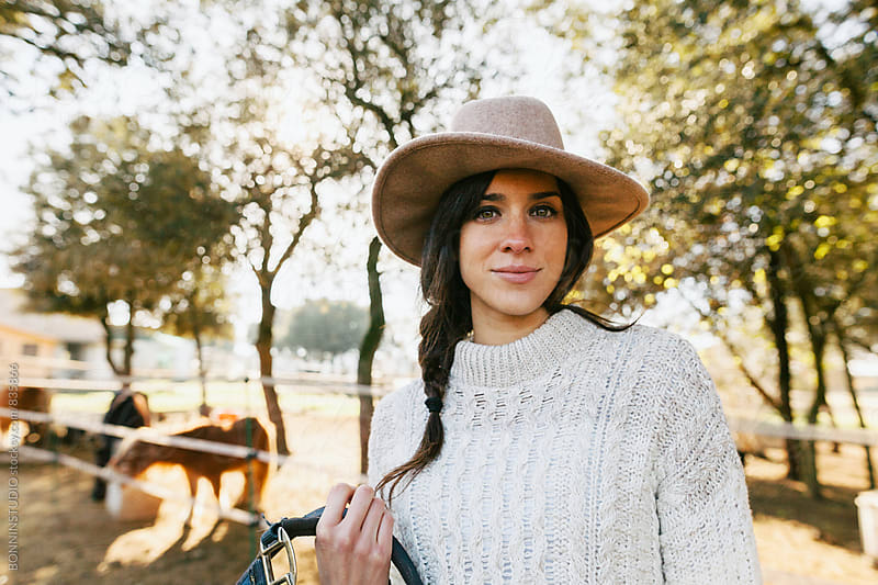 Portrait of a woman standing in a ranch. by BONNINSTUDIO for Stocksy United