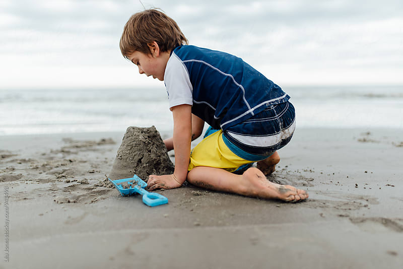 boy building sandcastle on beach by Léa Jones for Stocksy United