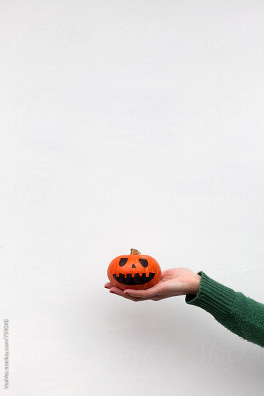 Female hand holiding a small Halloween pumpkin on a white wall  by Marija Mandic for Stocksy United