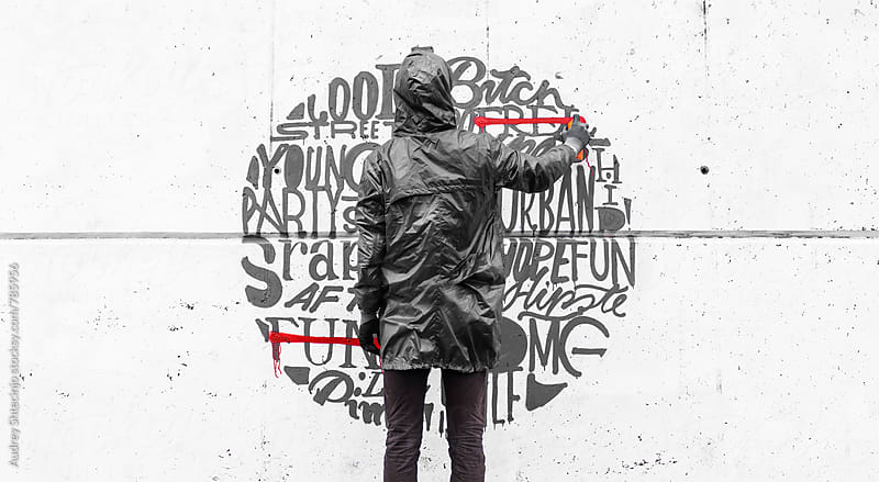 Street artist drawing various word with spraycan on wall by Audrey Shtecinjo for Stocksy United