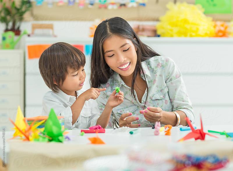 Preschooler and His Teacher Making Plasticine Animals by Lumina for Stocksy United