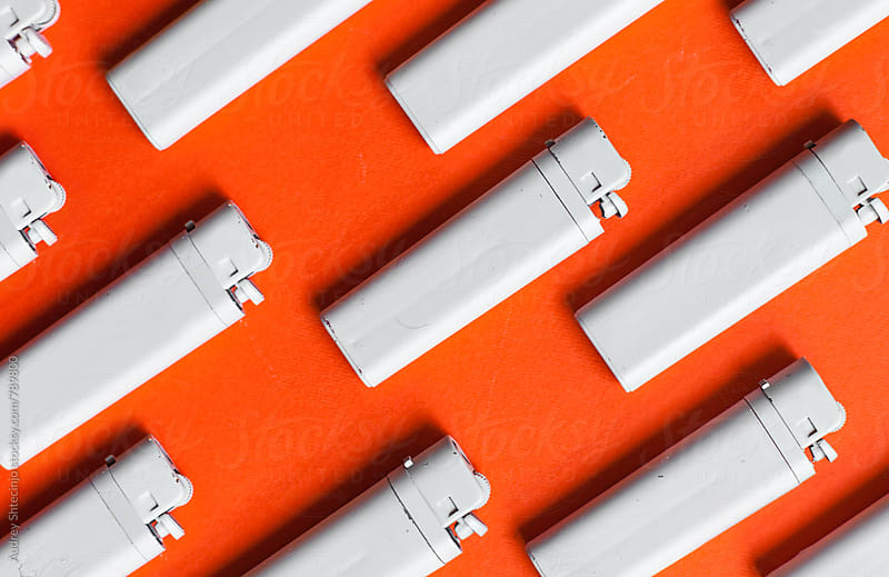 PAttern made from white lighters on red/orange background by Marko Milanovic for Stocksy United