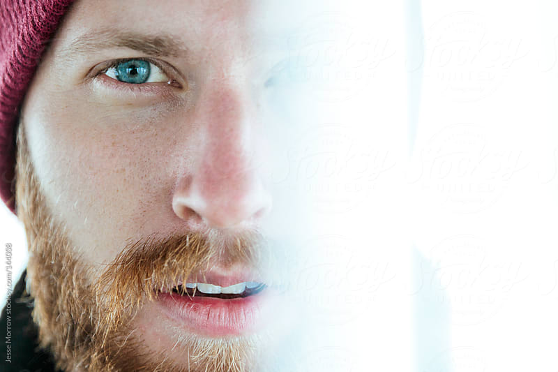 Portrait of a young man with a beard and blue eyes by Jesse Morrow for Stocksy United